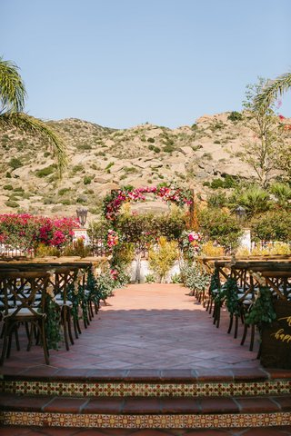wedding-ceremony-outside-hummingbird-nest-ranch-terracotta-tile-pink-greenery-bougainvillea-arch