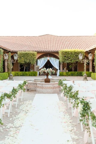 wedding-ceremony-outdoor-courtyard-setting-white-aisle-runner-greenery-pink-ribbon-apricot-arch