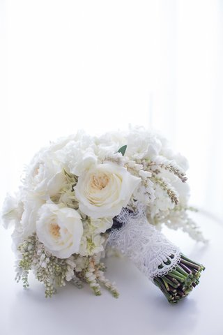 brides-bouquet-of-white-flowers-including-garden-roses-tied-with-lace-like-in-the-brides-dress