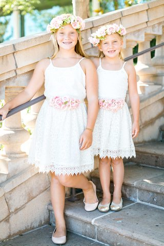 two-flower-girls-in-matching-white-lace-dresses-with-pink-rose-belt-flower-crowns-and-flats