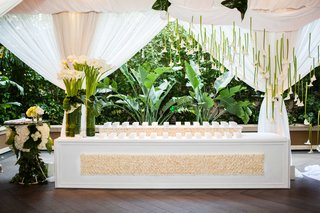 white-wedding-escort-card-table-with-cream-flowers-white-calla-lily-suspended-from-draped-ceiling