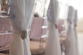clear-chiavari-chair-reception-table-with-white-chair-cover-sash-drapery-silver-brooch-decal