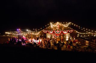 wooden-barn-lit-with-string-lights-and-decorated-with-red-white-and-blue-banners