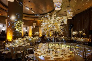 reception-space-with-multiple-colorful-lights-and-tall-floral-arrangements-in-white-and-gold