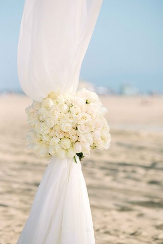beach-wedding-ceremony-with-white-rose-tiebacks-on-ceremony-canopy-of-white-fabric