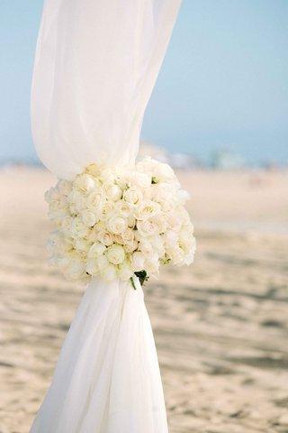 beach-wedding-ceremony-with-white-rose-tiebacks-on-ceremony-canopy-of-white-fabric