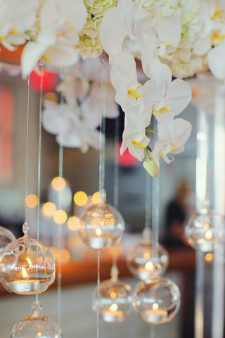 wedding-reception-with-tea-lights-in-glass-spheres-hung-from-arch-of-white-orchids-and-hydrangeas