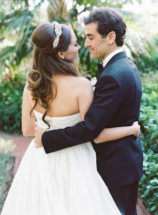 bride-in-strapless-reem-acra-a-line-wedding-dress-hugs-groom-with-one-arm-headpiece-half-up-hair