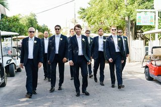 groom-and-groomsmen-in-suits-and-bow-ties-sunglasses-walking-on-bahamas-streets-harbour-island
