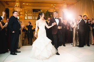 bride-and-groom-holding-hands-and-walking-on-dance-floor-guests-watching-chandeliers-taking-photos