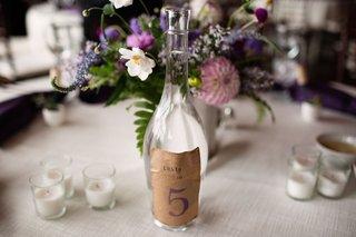 lyndsy-fonseca-wedding-with-diy-glass-bottle-kraft-paper-table-number-sticker