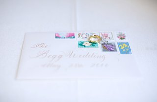 white-wedding-invitation-envelope-with-brightly-colored-pastel-stamps-and-wedding-rings