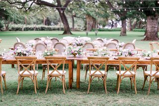 wedding-reception-outdoor-hawaii-string-lights-long-wood-table-vineyard-chairs-low-centerpieces