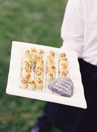 cucumber-cups-with-guacamole-and-mango-salsa-inside-rock-with-calligraphy-sign-on-tray
