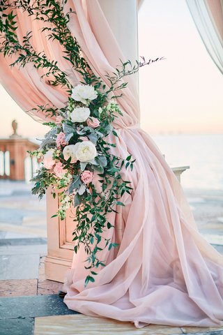 blush-drapery-on-chuppah-column-with-greenery-and-white-and-pink-flowers