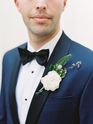 groom-with-navy-tuxedo-jacket-black-lapels-white-ranunculus-flower-fern-greenery-boutonniere