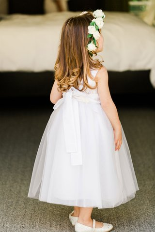 flower-girl-in-white-dress-bow-in-back-flats-curled-hair-white-rose-greenery-flower-crown-halo