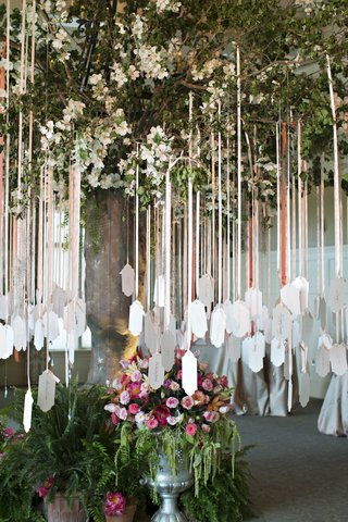 wedding-place-card-tree-with-white-flowers-and-place-cards-hanging-off-the-branches-from-ribbons
