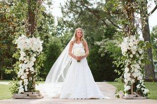 bride-under-floral-archway-in-a-line-wedding-dress