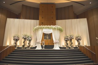 jewish-wedding-ceremony-with-white-fabric-chuppah-topped-with-white-flowers-tiebacks-at-posts