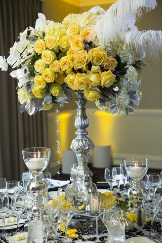 tall-flower-arrangement-on-silver-stand-with-yellow-roses-and-feathers
