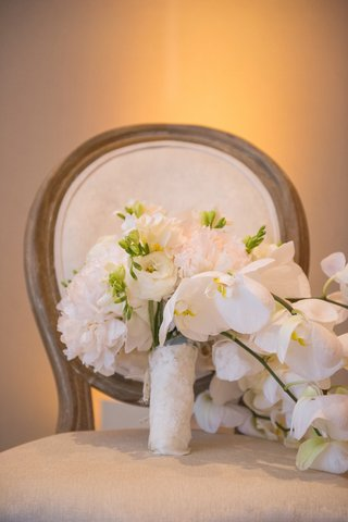 brides-bouquet-of-white-peonies-orchids-lisianthus-bound-by-lace