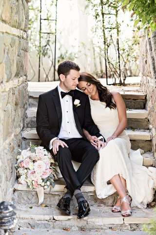 private-moment-between-bride-and-groom-before-wedding-ceremony-black-tuxedo-white-gown-sheath-dress