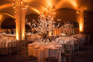 a-reception-space-with-circular-tables-featuring-white-table-linens-and-bright-uplighting