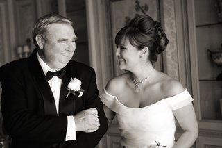 black-and-white-photo-of-bride-holds-on-to-arm-of-dad-wearing-tuxedo