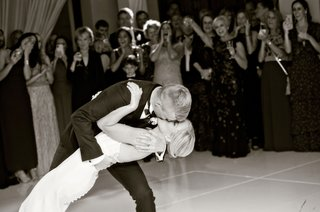black-and-white-photo-of-bride-and-groom-kissing-during-first-dance-at-wedding-romantic-dip