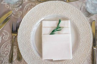 simple-white-plateware-concept-on-light-linens-with-embroidery-and-a-napkin-with-sprig-of-greenery