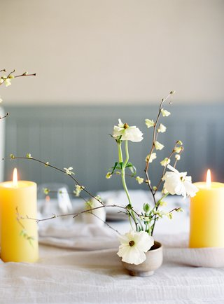 white-japanese-ranunculus-and-corylopsis-in-small-ceramic-bud-vases-yellow-pillar-candles
