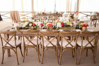 gold-box-centerpieces-holding-white-pink-and-orange-flowers-on-top-of-rustic-wood-tables-and-chair