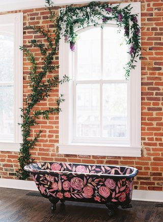 brick-wall-vine-on-window-black-claw-foot-bath-tub-with-pink-flowers-painted-rose