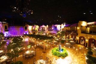 wedding-reception-that-looks-like-outdoor-venue-ballroom-high-ceilings-balcony-fountain-trees-lights