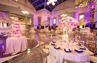 library-wedding-venue-with-violet-uplighting-white-tablecloths-gold-chairs-tall-centerpieces