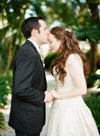 groom-holding-brides-hand-kiss-on-forehead-florida-wedding-beaded-bridal-gown-black-suit-half-up