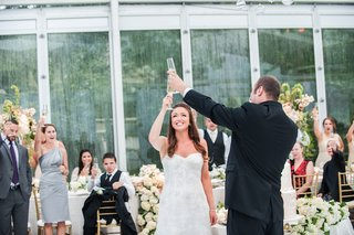 groom-in-black-tuxedo-toasts-with-bride-in-a-strapless-lace-monique-lhuillier-gown-in-glass-tent