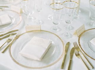 clear-charger-plates-rimmed-with-gold-gold-flateware-at-wedding-reception