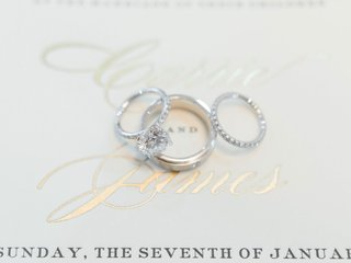 wedding-rings-on-gold-foil-invitation-solitaire-diamond-ring-with-matching-wedding-band