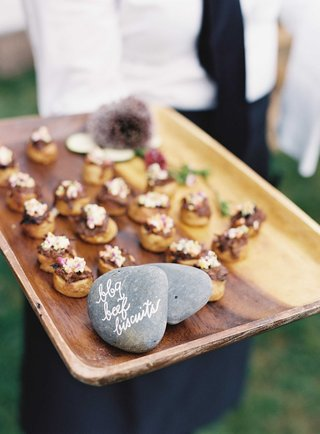 cocktail-hour-appetizer-on-wood-tray-with-rock-calligraphy-sign-barbecue-beef-biscuits
