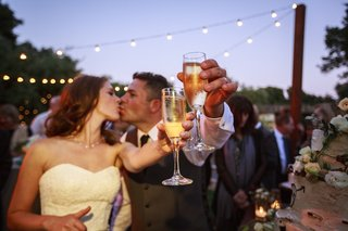 bride-and-groom-kiss-and-raise-glasses-of-champagne-at-outdoor-wedding-reception