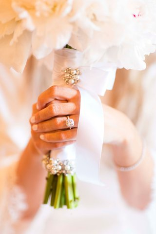 halo-engagement-ring-neutral-manicure-clutching-bouquet-white-ribbon-and-pearl-pins