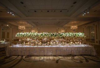 a-long-table-with-a-white-linen-featuring-tall-white-and-green-arrangements-connected-ghost-chairs