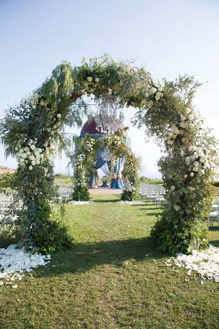 ceremony-at-resort-at-pelican-hill-with-arches-of-greenery-over-aisle-leading-to-rotunda