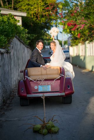 bride-and-groom-in-just-married-car-red-vehicle-with-bahamas-license-plate-coconuts-instead-of-cans