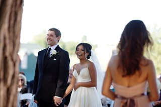bride-in-a-wedding-dress-with-spaghetti-straps-holds-hands-with-groom-in-black-suit-and-tie