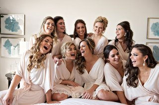 bride-and-bridesmaid-laughing-on-bed-at-casa-del-mar-in-santa-monica-before-wedding-ceremony