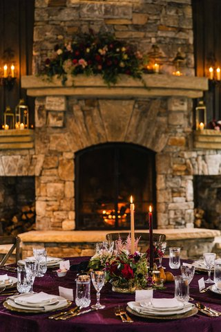 cozy-rustic-tablescape-with-purple-table-linens-and-low-floral-arrangements-in-front-of-fireplace