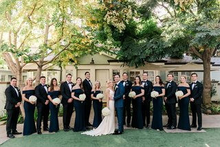 groom-in-blue-suit-with-bride-bridesmaids-in-navy-blue-off-shoulder-gowns-groomsmen-in-suits-bow-tie